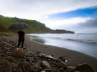 A woman holds an umbrella on the beach of Pololu Valley as it begins to rain, Hawi, Big Island.