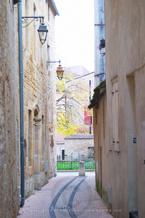 A curving street in the old town with old stone houses, leading to the main town square. Bergerac Dordogne France