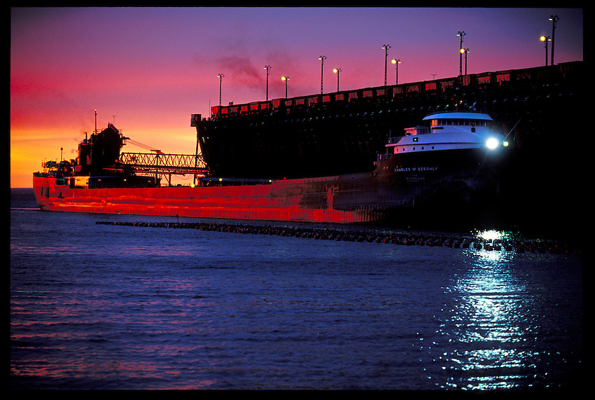THE FREIGHTER CHARLES M. BEEGHLY SHINES A LIGHT AS IT DOCKS AT THE LAKE SUPERIOR & ISHPEMING RAILROAD IRON ORE DOCK IN MARQUETTE, MICHIGAN AT DUSK.