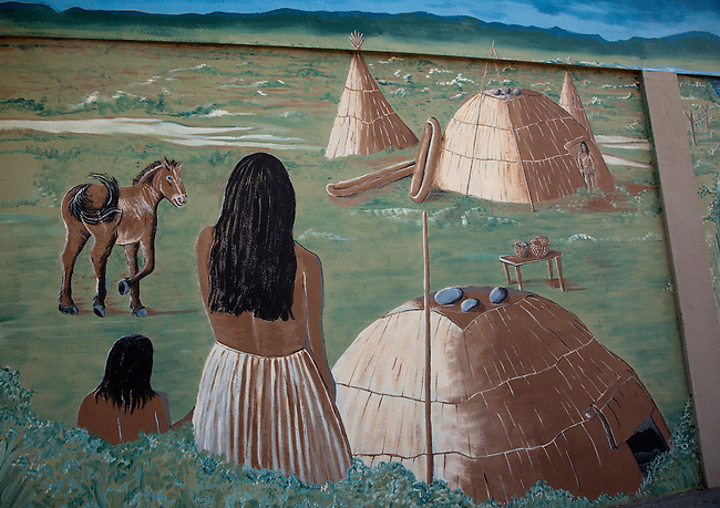 Mural of a Klamath village with dwellings made from tule reeds and tule canoes
