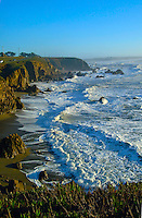 The rocks and surf of the Sonoma Coast State Beach near Bodega Bay California with cars traveling on Highway One on the cliff above.
