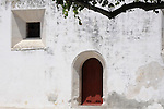 A white wall with a red door, detail of the Royal Palace in Sintra, Portugal.