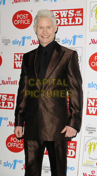 RHYDIAN ROBERTS.Children's Champions Awards 2009 at the Grosvenor House Hotel, Park Lane, London, England..March 4th 2009.half 3/4 length brown black shiny suit pattern .CAP/CAN.©Can Nguyen/Capital Pictures.