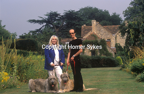 Dwina Gibb and Robin Gibb of the pop group Bee Gees 2000s at their home in the Home Counties UK. Seen here in their garden with their two Irish Wolf Hounds.