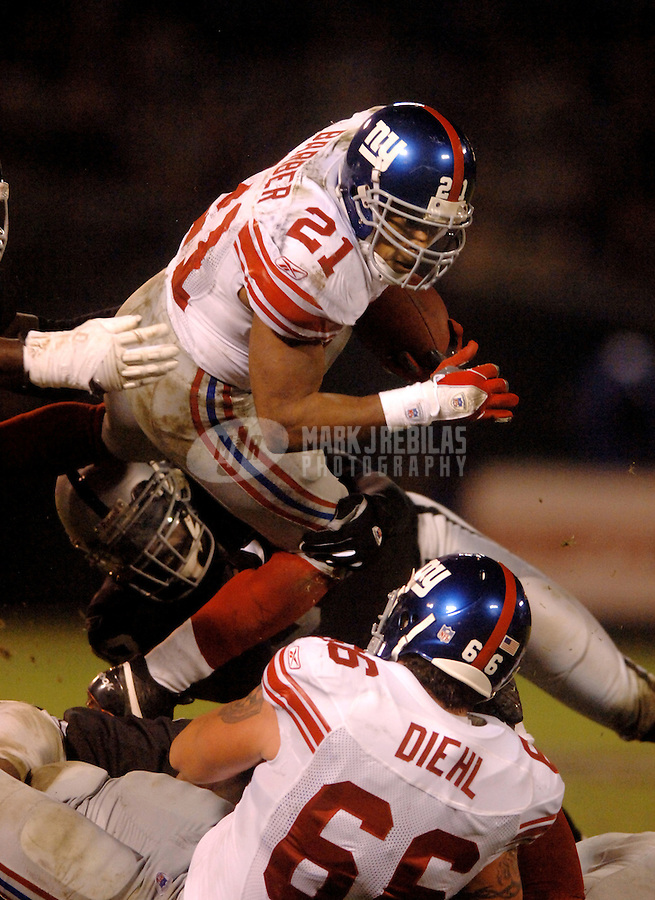 Dec. 31, 2005; Oakland, Calif, USA;  New York Giants running back (21) Tiki Barber leaps over an Oakland Raiders defender in the second quarter at McAfee Coliseum. Mandatory Credit: Photo By Mark J. Rebilas