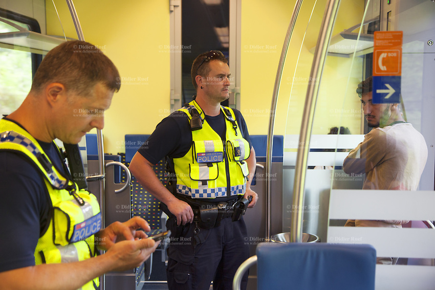 Switzerland. Canton Ticino. Two police officers from TPO (Transport Police) on a TILO train between Lugano and Chiasso.The policemen check the identity of a Romanian Romani man travelling without ticket. On the next station, the man was expelled from the train. The Romani (also spelled Romany, Roma, Roms or Rroms, are a traditionally nomadic ethnic group. TPO (Transport Police) is the Swiss Federal Railways Police. Swiss Federal Railways (German: Schweizerische Bundesbahnen (SBB), French: Chemins de fer fédéraux suisses (CFF), Italian: Ferrovie federali svizzere (FFS)) is the national railway company of Switzerland. It is usually referred to by the initials of its German, French and Italian names, as SBB CFF FFS. TILO (Treni Regionali Ticino Lombardia) creates efficient train connections between the towns in the canton Ticino.12.06.2017 © 2017 Didier Ruef