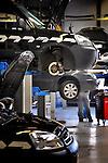 In de garage van een autodealer staan diverse auto klaar voor de monteur voor het onderhoud en reparatie van een auto van een klant.