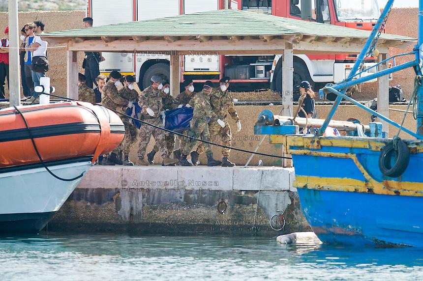 Soldati dell'Esercito Italiano trasportano una delle vittime del naufragio che è costato la vita a più di 300 persone. Italian soldiers carry the body of a victim of the ship of immigrants that sank on October 3, 2013 in Lampedusa.