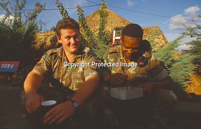 PSMILIT27021.Defence Force. Military.  SADF Two men in uniform sharing a meal '96. Soldiers  in camoflauge. Mix race.©Per - Anders Pettersson / iAfrika photos