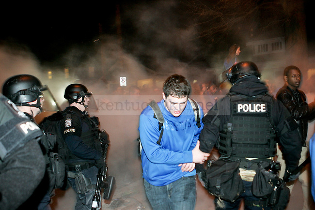 Police in riot gear clear UK fans away from a fire while UK fans celebrate after UK beat Wisconsin in Lexington, Ky., on Sunday, April, 6, 2014. Photo by Jonathan Krueger | Staff