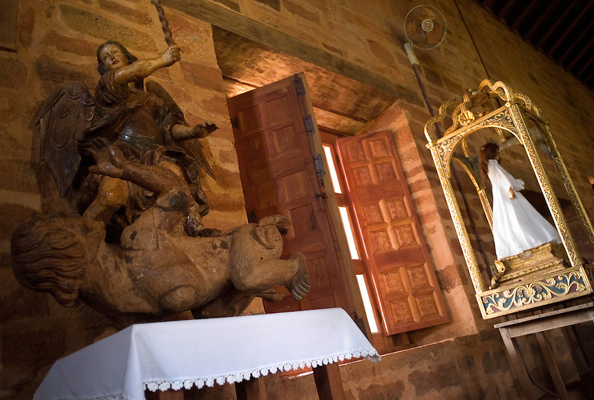 Michael the Archangel slays a heraphrodite devil in a Guaraní-carved statue in the Jesuit mission church at San Cosme y Damian, Paraguay. Scores of Jesuit missions in the area where Paraguay, Argentina and Brazil meet were built in the 17th century and abandoned when the Jesuits were expelled in the 18th century. Ruins of some of these missions still haunt hilltops in the region. The main church at San Cosme y Damian collapsed more than a century ago, but the community still uses the first provisional church built on the site. (Kevin Moloney for the New York Times)