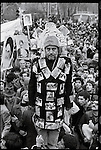 """A pro-Khomeini demonstrator dons a jacket decorated with photographs of victims of the shah's repression and a hat that reads """"crown of the martyrs."""" Tehran, January 19, 1979."""