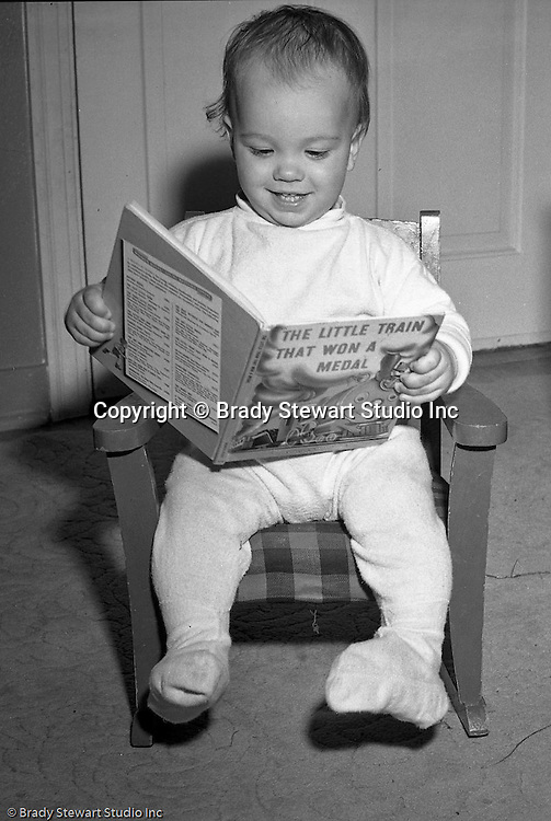 """Pleasant Hills PA:  Brady Stewart Studio participated in a national promotion for American Hardware Catalog Cover - 1950.  The contest asked for submissions to include a child reading a book at night time.  In this image, Brady Stewart III is reading the """"The Little Train that Won a Metal""""."""