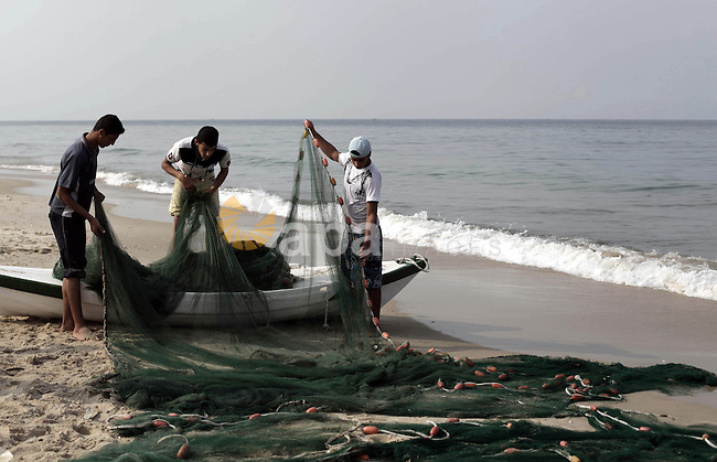 Palestinian fishermen retrieve their net at the beach of Gaza City, on November 18, 2013. Israel restricted the fishing zone to three nautical miles following the kidnapping of Israeli soldier Gilad Shalit in 2007. The Oslo Accords signed in 1993 with the Palestinian Authority stipulate that Gaza s fishing zone should extend to 20 nautical miles. The zone was then extended to six nautical miles as part of the Egyptian-brokered cease-fire in November 2012, but Israel intermittently reduce it to three nautical miles each time violence flares. Photo by Ashraf Amra