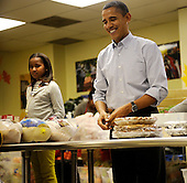 United States President Barack Obama packs and gives bags of food to area residents, with the help of his daughter Sasha, left, at Martha's Table on Wednesday, November 24, 2010, in Washington, DC.  .Credit: Leslie E. Kossoff - Pool via CNP