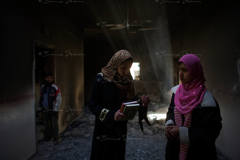 Al Kuza'ah, Gaza Strip, Jan 14 2009.Aslam Nejjar, 18, in pink and her sister Fadia Nejjar, 20 in the ruins of their home. An Israeli tank assault on this village left 10 people dead and many more wounded; dozens of homes are destroyed, many burned by white phosphorus, active patches of which can still be found in many area inside the village 36 hours after the attack..Hundreds of shocked inhabitants collect what they can from their destroyed houses and are fleeing away to safer areas.