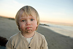 Young child with a mouth full of sand