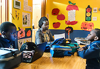 Mary Kuanen working at Blessed Sacrament Catholic School with her children Bang Malual (age 13, left), Emmanuel Malual (age 7) in Denver, Colorado, Friday, October 21, 2016. Kuanen a refugee from Sudan moved to Denver 11 years ago with her husband and children. Five years ago her husband was murdered in a mistaken identity gang shooting. <br /> <br /> Photo by Matt Nager