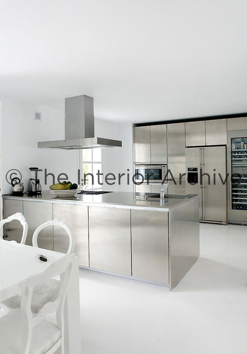 The contemporary stainless steel kitchen reflects light around the open plan kitchen/dining area