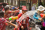"""Apr. 13, 2010 - Bangkok, Thailand: Thais squirt each other with water on Songkran in central Bangkok Tuesday. Songkran is the Thai New Year's holiday, celebrated from April 13 - 15. This year's official celebrations have been cancelled because of the Red Shirt protests but Thais are still marking the holiday. It's one of the most popular holidays in Thailand. Songkran originally was celebrated only in the north of Thailand, and was adapted from the Indian Holi festival. Except the Thais throw water instead of colored powder. The throwing of water originated as a way to pay respect to people, by capturing the water after it had been poured over the Buddhas for cleansing and then using this """"blessed"""" water to give good fortune to elders and family by gently pouring it on the shoulder. Among young people the holiday evolved to include dousing strangers with water to relieve the heat, since April is the hottest month in Thailand (temperatures can rise to over 100°F or 40°C on some days). This has further evolved into water fights and splashing water over people riding in vehicles. The water is meant as a symbol of washing all of the bad away and is sometimes filled with fragrant herbs when celebrated in the traditional manner. Photo by Jack Kurtz"""