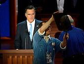 Mitt Romney, Republican Presidential Candidate, looks on as a staffer adjusts the teleprompter as he participates in a microphone check prior to the start of the day's proceedings at the 2012 Republican National Convention in Tampa Bay, Florida on Thursday, August 30, 2012.  .Credit: Ron Sachs / CNP.(RESTRICTION: NO New York or New Jersey Newspapers or newspapers within a 75 mile radius of New York City)