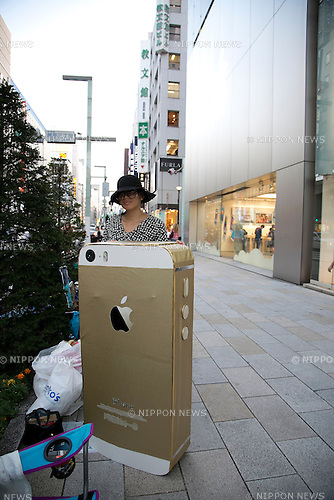 A woman waits and shows a big iPhone in front of the Apple Store in Ginza, to buy the new iPhone 5s and lower-cost iPhone 5c, September 17, 2013. During the typhoon Man-yi, the 18th of the season, lashes on Japan this September 16, 2013, Apple fans waited inside the store to protect of the powerful typhoon. According to Apple the mobile phones will be available in Japan, U.S. and other seven countries from September 20. (Photo by Rodrigo Reyes Marin/AFLO)