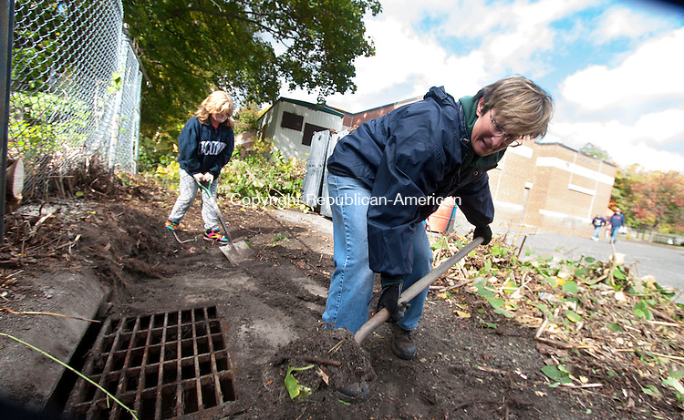 WINSTED, CT - 17 OCTOBER 2015 - 101715JW02.jpg -- Cleanup volunteers Nora Mocarski and Madison McLellan age 9 shovel dirt away from a storm drain they uncovered while cleaning up an area behind Hinsdale School Saturday morning. Jonathan Wilcox Republican-American