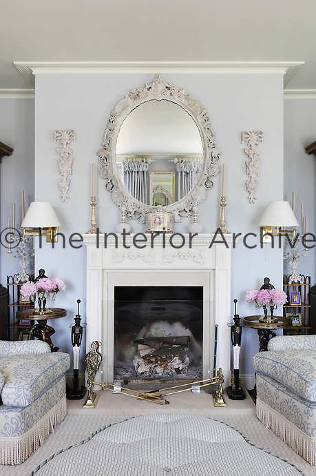 An elaborately carved mirror and boiserie decorations hang above the fireplace of the pale blue living room