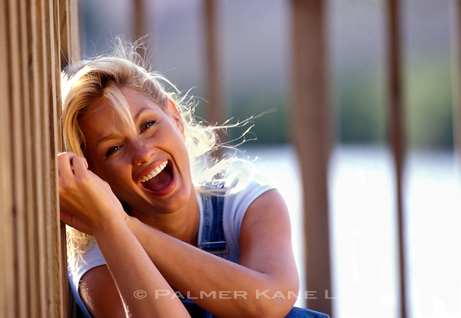 Blonde woman sitting on floor of deck laughing