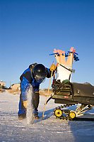 Volunteer drills hole in ice to put in wood stake trail markers on Unalakleet River near Unalakleet