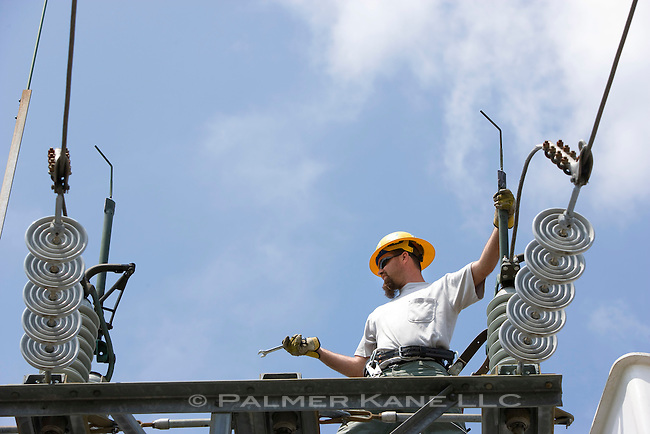 """Utility workman installing updated components to a """"city gate"""" electrical substation Linemen working on a city gate"""
