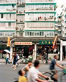 CHINA, Hangzhou, people riding bicycles in an urban shopping area