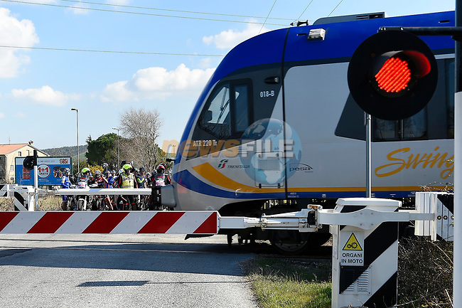 The peloton are held up by a train during Stage 6 of the 2017 Tirreno Adriatico running 168km from Ascoli Piceno to Civitanova Marche, Italy. 13th March 2017.<br /> Picture: La Presse/Fabio Ferrari | Cyclefile<br /> <br /> <br /> All photos usage must carry mandatory copyright credit (&copy; Cyclefile | La Presse)