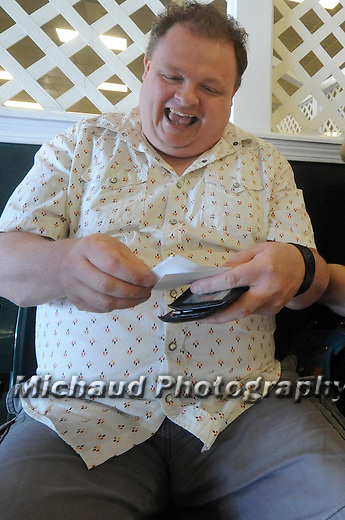 (Boston Ma 060615) Jason Fischer, 44,  of Malden, excited for the start of the big race, looks over his tickets, including American Pharoah, prior to the Belmont Stakes, Saturday, June 6, 2015, at Suffolk Downs in Boston. Herald Photo by Jim Michaud