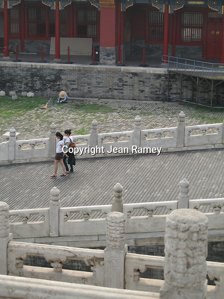 Tourists walk through Forbidden City as a worker labors nearby