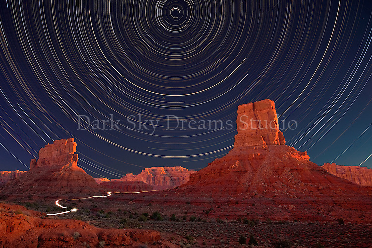 The headlights of a lone 4WD pickup winds along the rugged track between the craggy monoliths of the Valley of the Gods, meanwhile, the stars wheel through the nighttime sky in this sunset to sunrise time-lapse composition.