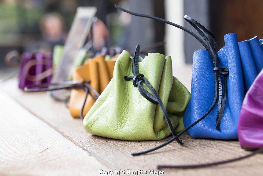 handmade leather purses in bright colors on display in an outdoor market in the Czech Republic