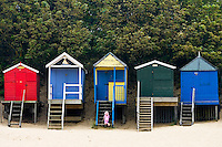 Young girl explores beach huts in Wells-Next-The-Sea, Norfolk, United Kingdom
