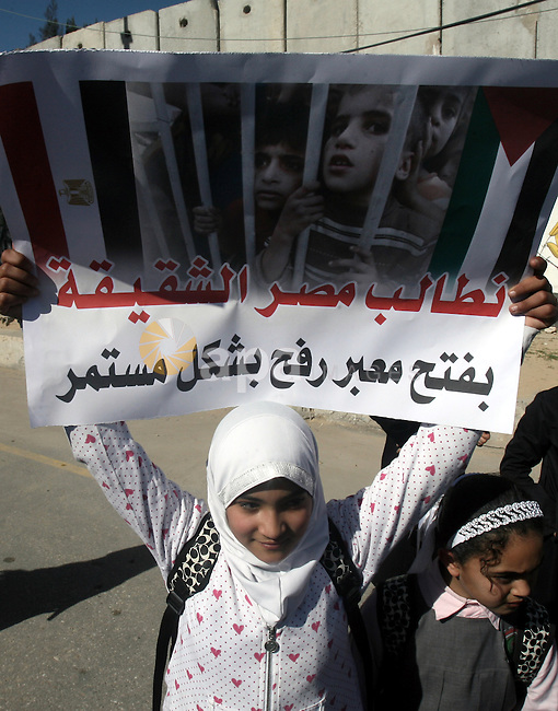 Palestinian children carry placards during a rally in front of the Rafah border crossing with Egypt in the southern Gaza Strip on January 29, 2014, demanding the permanent and unconditional opening of the crossing. Egypt occasionally permits people to enter and leave Gaza, but has refused to open on a permanent basis the only border crossing in the Hamas-run Palestinian coastal strip not controlled by Israel. Photo by Eyad Al Baba