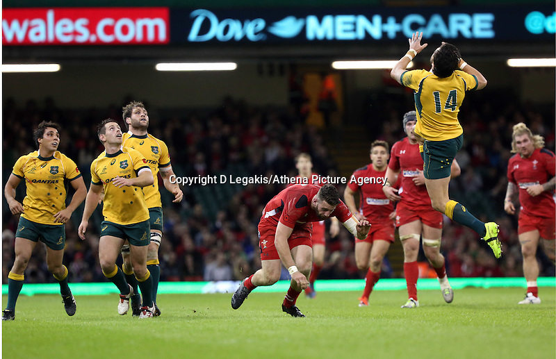 Pictured: Alex Cuthbert of Wales (C) is tripped down by Adam Ashley-Cooper of Australia (R) who jumps for the ball Saturday 08 November 2014<br /> Re: Dove Men Series rugby, Wales v Australia at the Millennium Stadium, Cardiff, south Wales, UK.