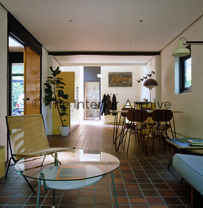 The open-plan living space has a floor of terracotta tiles leading from the sitting room through to the kitchen