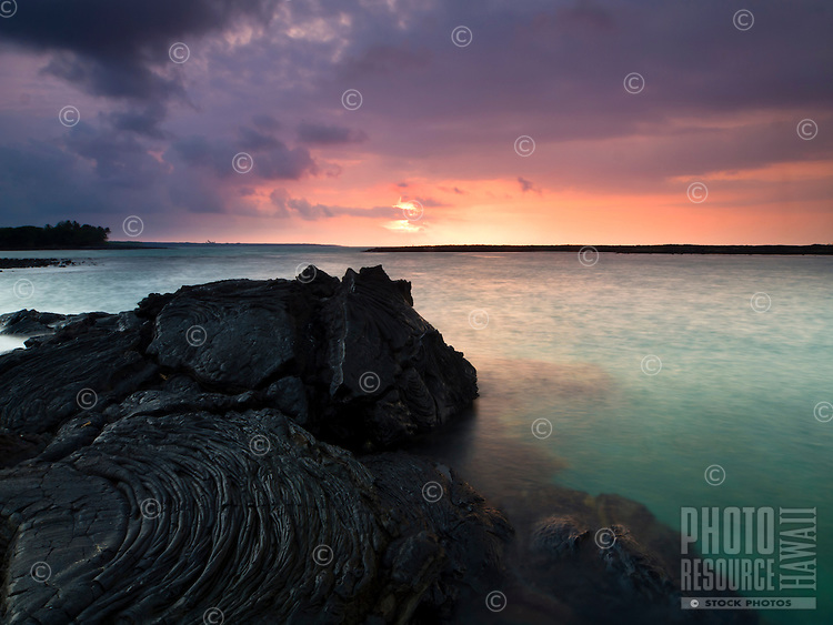 A colorful sunset and the turquoise waters of Kiholo Bay provide a deep contrast with the dark folds of lava rock along the bay's shoreline, Big Island.