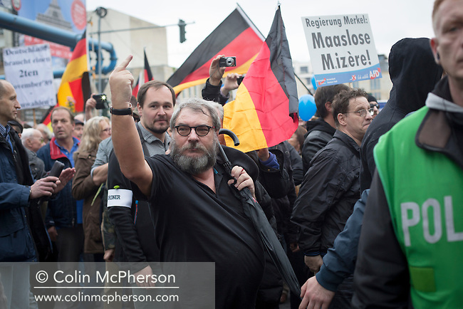 A man gestures to counter-demonstrators during a march through the streets of Berlin by the Alternative für Deutschland (AfD) political party. Around 5000 supporters of the AfD took part in the march and rally calling on German Chancellor Angela Merkel to halt the influx of refugees into the country. Around one million refugees from the Middle East and north Africa arrived in Germany during 2015, 50,000 of whom came to Berlin.