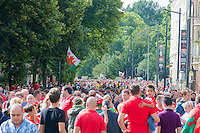 CARDIFF, UK. 8th July 2016. Thousands of fans lined the street to welcome the Welsh football team home with a public celebration event after reaching the semi-final of the Euro 2016 championship. After landing at Cardiff airport, an open-top bus parade took them through the city centre.