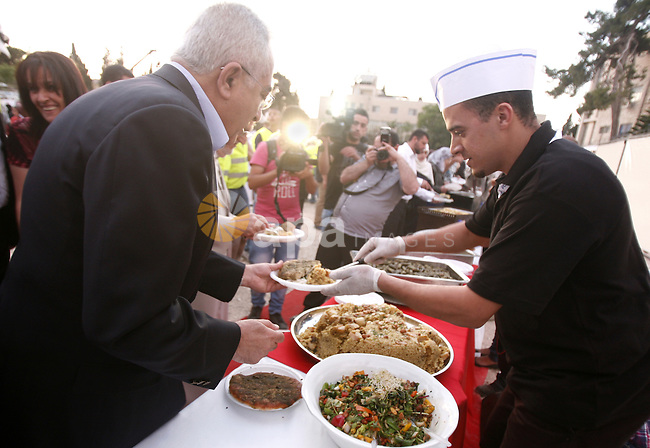 Palestinian Prime Minister Salam Fayad fills his plate with a local salad dish after receiving the certificate for the longest buffet of natural and organic food which registered a new guinness world record, on May 26, 2012 in Arab east jerusalem. The Palestinian banquet, prepared by Jerusalem locals, measured 202 metres. Photo by Mahfouz Abu Turk