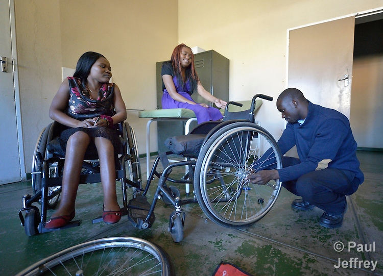 Wilson Bopoto adjusts Irene Phiri's wheelchair at the National Rehabilitation Centre in Ruwa, Zimbabwe, as Hope Ranganayi (left) watches. The Centre assembles and fits wheelchairs provided by the Jairos Jiri Association with support from CBM-US.