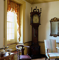 An antique grandfather clock stands in a corner of the drawing room