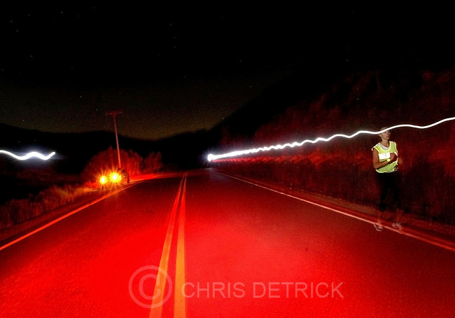 Logan,Utah--6/18/2005- .At 2:03 a.m., Erin McCormick, 24, of New York, N.Y., races up South Highway 66 near Porterville during section 18 of the race. During the night section of the race, competitors were required to wear a head lamp or flashlight and wear a  reflective vest to be more visible to oncoming traffic. This was McCormick's 15th mile of the day during the two day, 170 mile long Wasatch Back Relay Race.  100 teams with either six or 12 members competed in the race which started at the Hardware Ranch in Logan and  ended in Park City. The race was split into 36 section, each with varying lengths and difficulties,  in which the team members each  took turn running ..Photo By: Chris Detrick /Salt Lake Tribune.