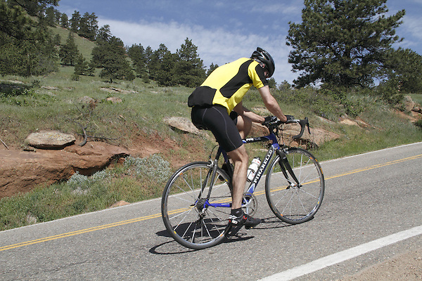 Caucasian male biking uphill on Flagstaff Mountain Road west of Boulder, Colorado. .  John leads private photo tours in Boulder and throughout Colorado. Year-round.