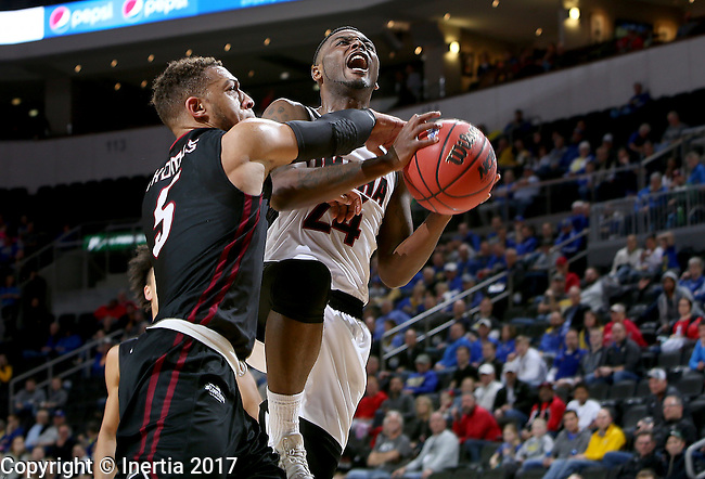 SIOUX FALLS, SD: MARCH 6: Tra-Deon Hollins #24 from Omaha is fouled while taking the ball to the basket by Kellon Thomas #5 from IUPUI during the Summit League Basketball Championship on March 6, 2017 at the Denny Sanford Premier Center in Sioux Falls, SD. (Photo by Dave Eggen/Inertia)